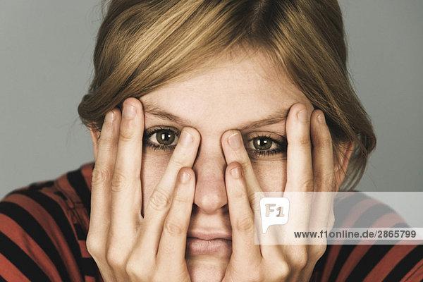 Junge Frau  Hände aufs Gesicht  Portrait  Nahaufnahme