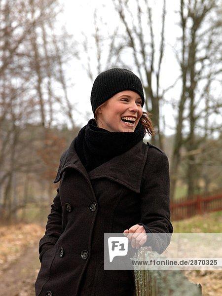 Eine junge Frau stand neben einem Zaun Schweden.
