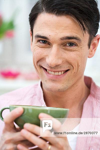 Ein Mann  hält ein eine Tasse Tee Schweden.