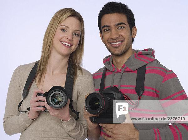 Portrait junger Fotografen mit Kameras  Studioaufnahme