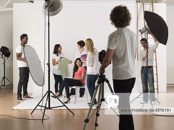 Gruppe von jungen Menschen in Fotostudio bei Vorbereitung zu Fototermin