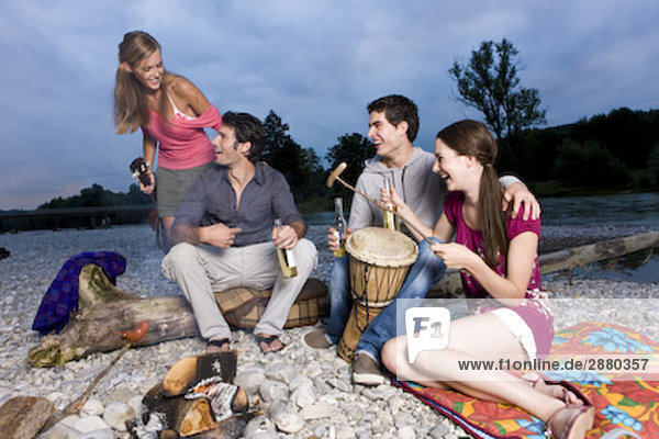 group of friends enjoying beer and sausages at party on riverbank in summer