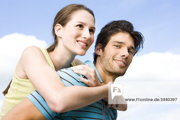 portrait of young man giving girlfriend piggyback ride