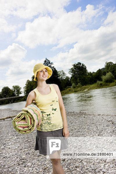 junge Frau mit gelben Mütze entlang River im Sommer