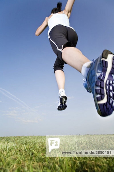 low angle view of young woman jogging through park