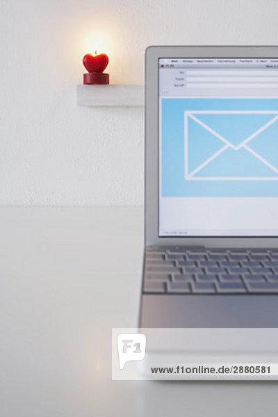 Stillleben mit Laptop-Computer mit Herz geformt Kerze brennen im Hintergrund