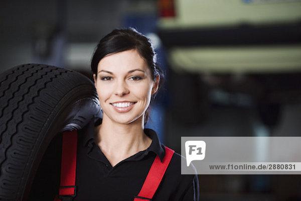 Porträt von weiblichen Mechaniker mit Reifen
