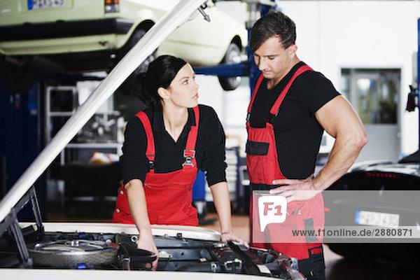 weibliche und männliche Mechaniker mit Diskussion im garage