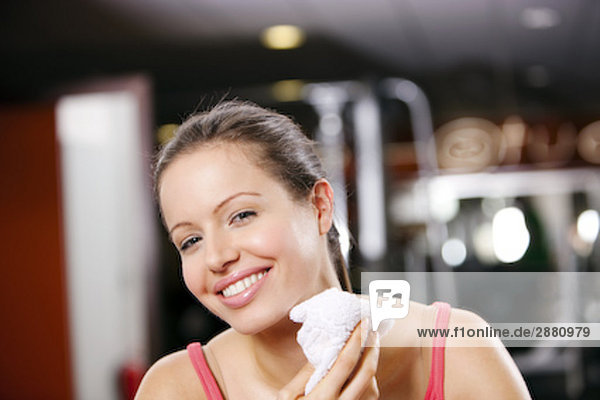 portrait of young woman with towel in gym