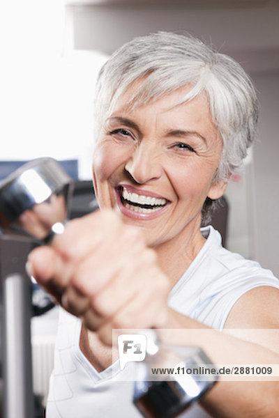 Portrait reife Frau Training mit dumb Glocken
