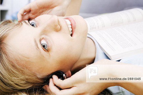 Portrait einer jungen Frau auf Rücken liegend mit Buch und Musik zu hören