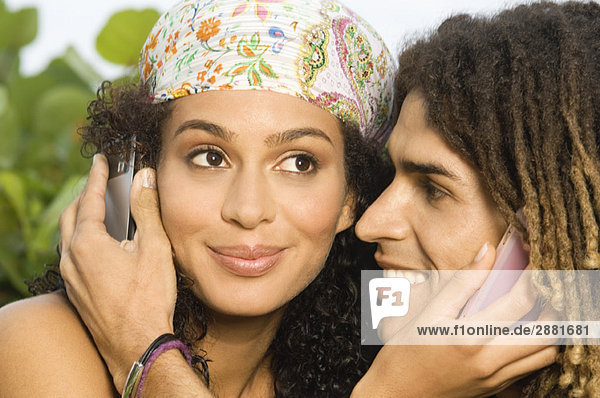 Close-up of a couple using mobile phones