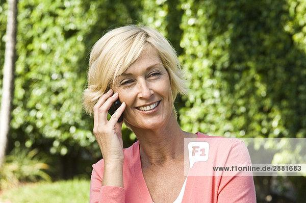 Frau spricht auf dem Handy und lächelt