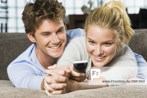 Paar mit Fernbedienung und Lächeln