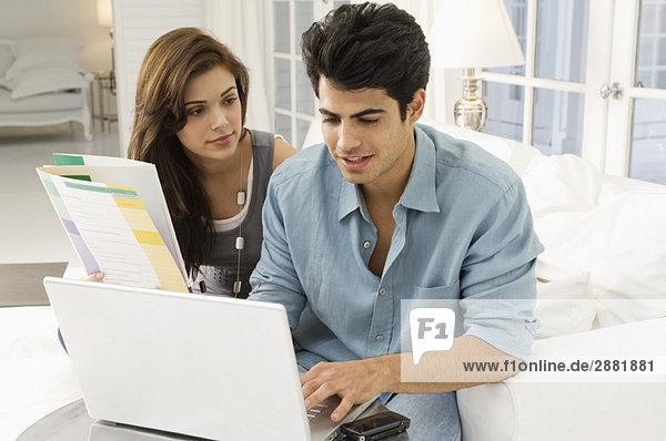 Mann mit einem Laptop und einer Frau  die neben ihm sitzt.