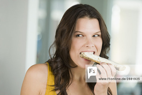 Close-up of a woman eating a bread