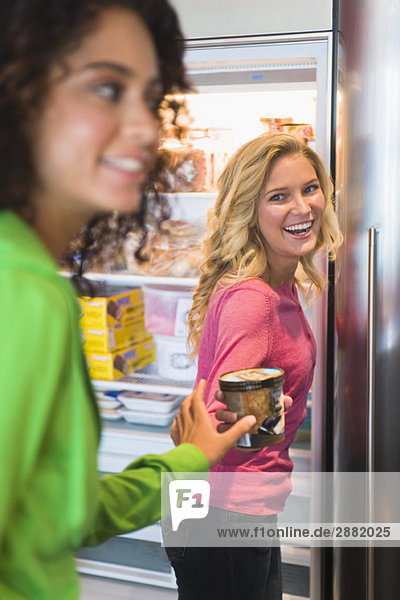 Frau  die ihrer Freundin aus dem Kühlschrank eine Konservendose gibt.