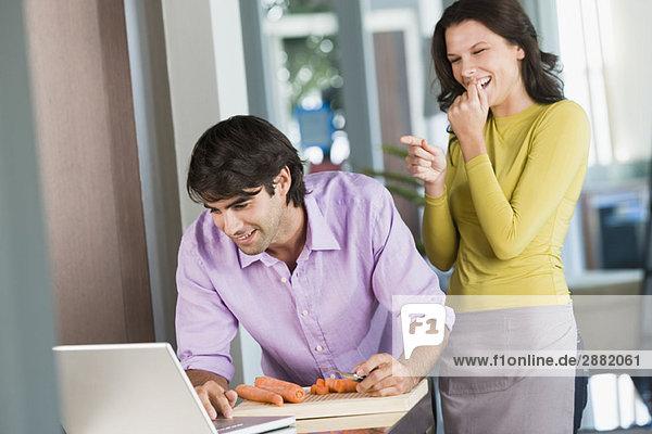 Mann kocht mit dem Rezept auf einem Laptop und eine Frau lacht ihn aus.