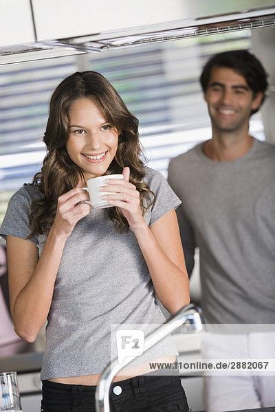 Frau trinkt Tee mit einem Mann im Hintergrund