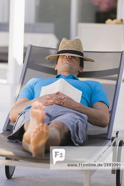 Mann schläft auf einem Sessel