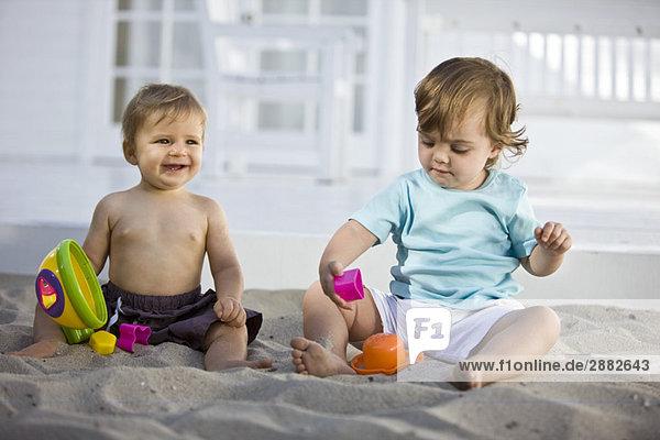 Zwei Babys spielen mit Spielzeug im Sand