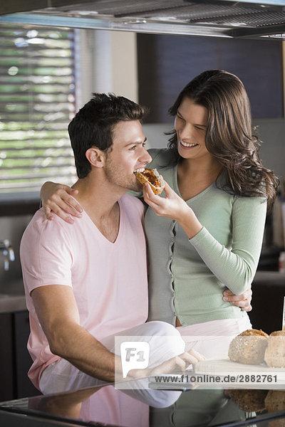 Frau füttert einen Mann mit Frühstück