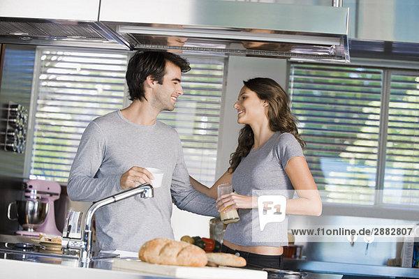 Ein Paar frühstückt und lächelt sich in der Küche an.