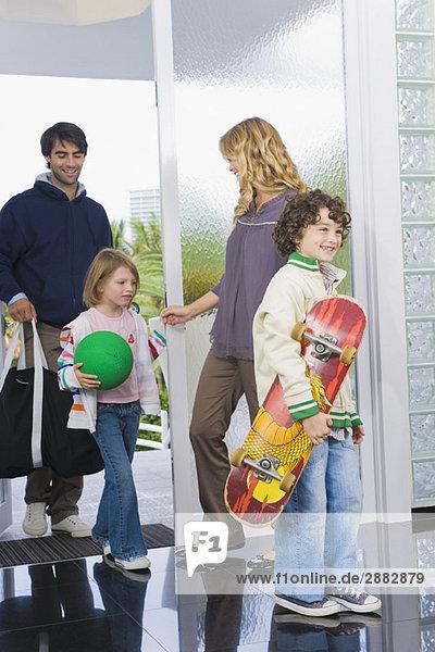 Mann betritt das Haus mit seinen Kindern