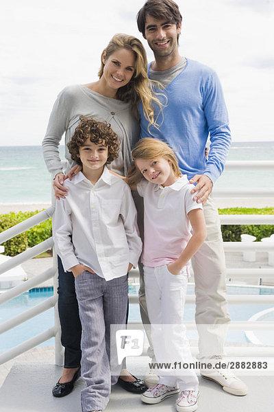 Paar mit ihren Kindern an einem Geländer stehend