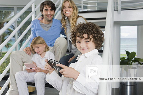 Eltern sitzen mit ihren Kindern auf der Treppe und spielen Videospiele.