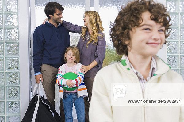 Junge lächelt mit seinen Eltern im Hintergrund