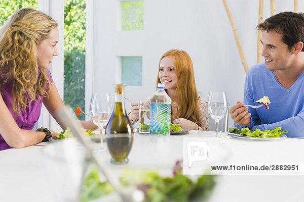 Familie beim Mittagessen und Lächeln
