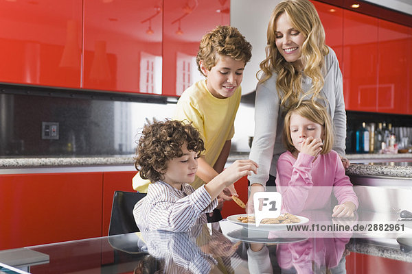 Woman with her children eating cookies in the kitchen