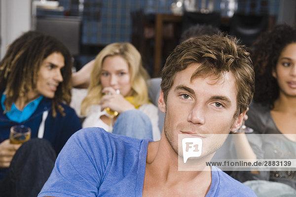 Porträt eines Mannes mit seinen Freunden bei einer Party