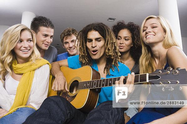 Mann sitzt mit seinen Freunden und spielt Gitarre.