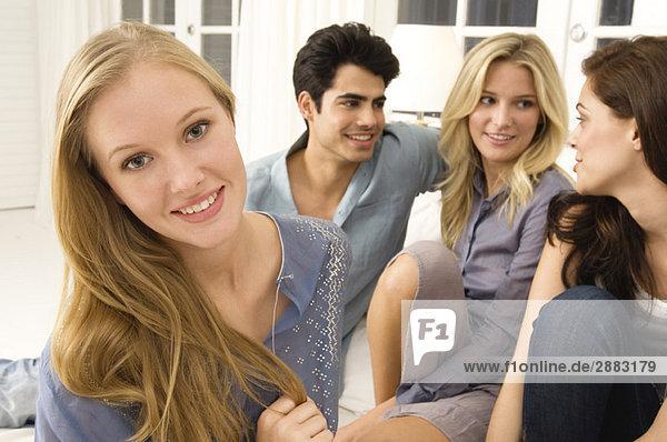 Vier Freunde klatschen in einem Wohnzimmer