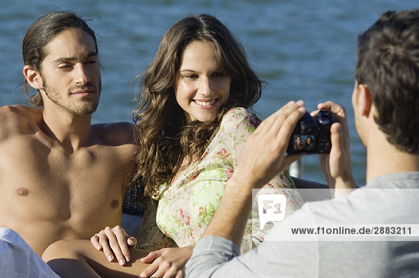 Ein Mann fotografiert seine Freunde mit einer Digitalkamera.