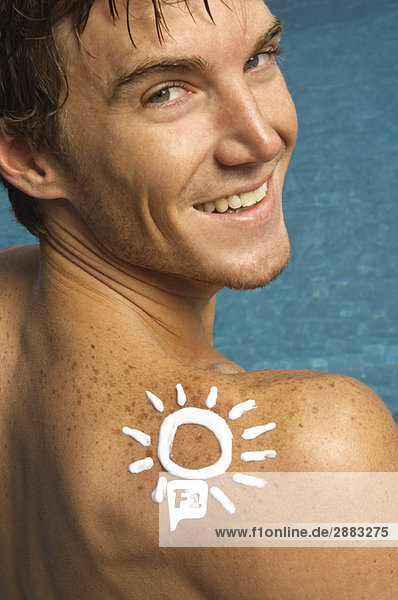 Mann mit Sonnenform auf der Schulter am Beckenrand