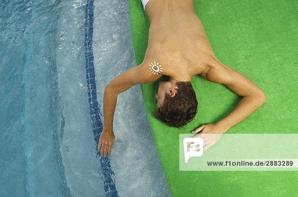 Hochwinkelansicht eines Mannes beim Sonnenbaden am Pool