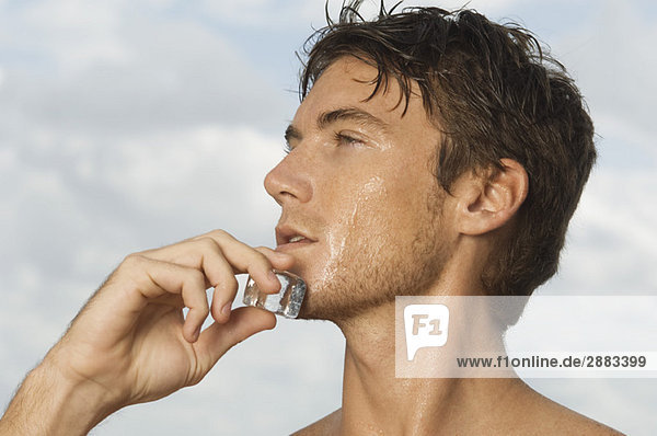 Mann reibt sich einen Eiswürfel ins Gesicht Mann reibt sich einen Eiswürfel ins Gesicht