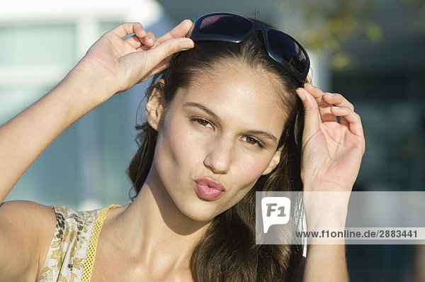 Portrait of a woman adjusting sunglasses and puckering her lips