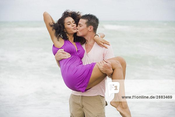 Mann  der eine Frau am Strand trägt und küsst.