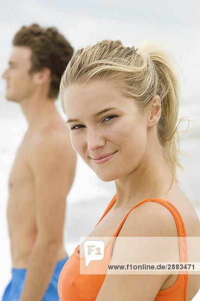 Porträt einer Frau  die mit einem Mann am Strand steht.