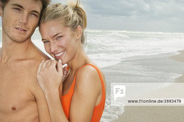 Porträt eines am Strand lächelnden Paares
