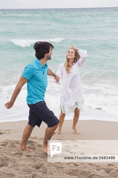 Paar Wandern mit Händchenhalten am Strand