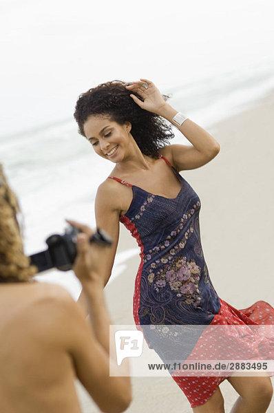 Mann macht ein Video von einer tanzenden Frau am Strand
