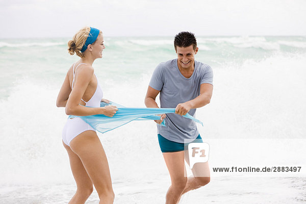 Mann mit Sarong einer Frau am Strand