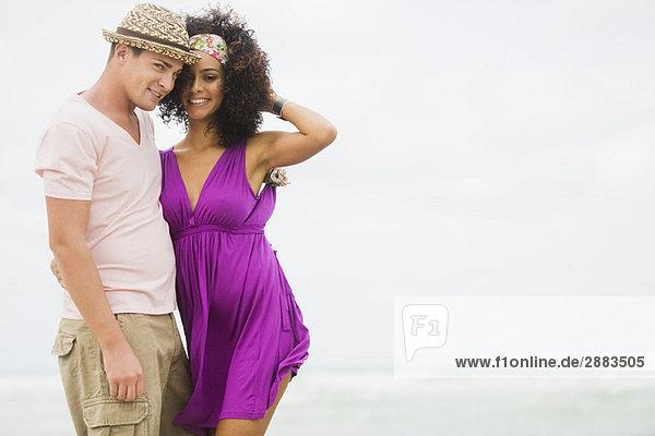 Paar am Strand stehend und lächelnd
