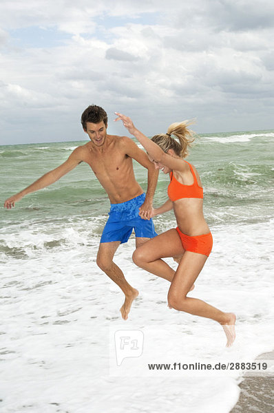 Paar beim Händchenhalten und Springen am Strand