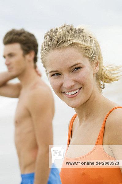 Frau steht mit einem Mann am Strand.